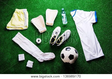 Soccer ball, cleats and various football stuff against artificial turf. Studio shot on green background. Flat lay.