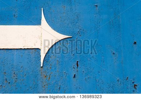 White Metal Arrow On Rusted Blue Metal