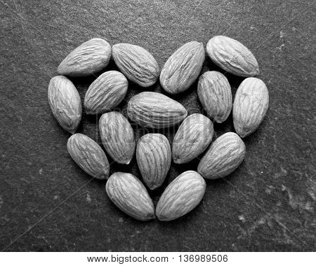 Black and white almonds in heart shape on slate