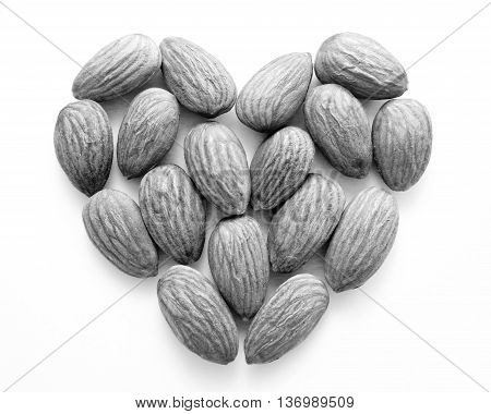 Black and white almonds in heart shape on white background
