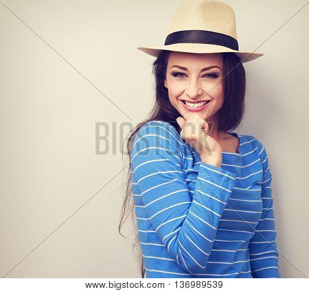Beautiful Long Hair Laughing Woman In Blue Top And Straw Hat Looking Happy With Hand Under Face. Vin
