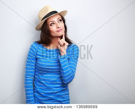 Grimacing Young Lady In Summer Hat Thinking And Looking Up On Blue Background