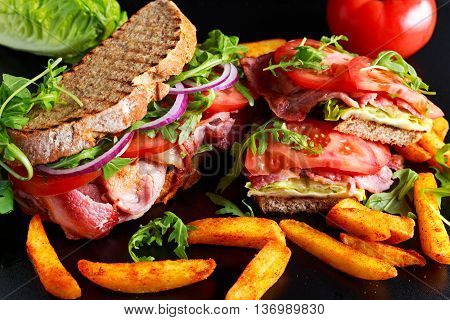 Fresh homemade BLT sandwich on grilled bread with bacon, lettuce, beef tomato, red onions, wild rocket and chips.