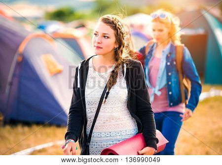 Two beautiful teen friends arriving at summer music festival, girl with backpack and camping mat