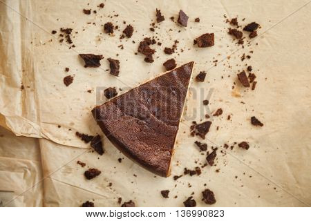 Piece Of Chocolate Cake With Crumbs On Craft Paper
