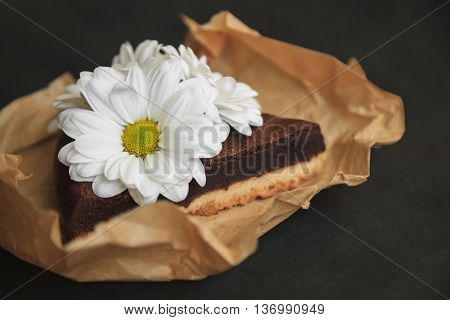 Piece Of Chocolate Cake With Flowers On Craft Paper