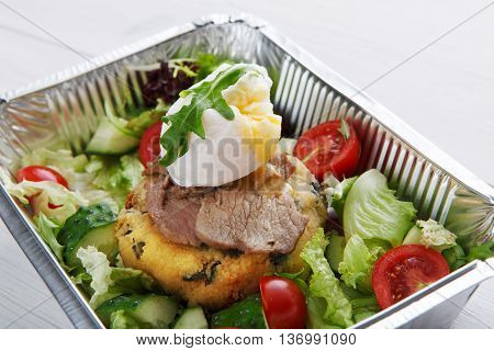 Restaurant food delivery in foil box. Poached egg with runny yolk closeup on veil steak medium rare with fresh vegetable salad and couscous cushion. Dish take away closeup, healthy meal.