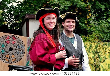 Mount Hope Pennsylvania - October 17 2015: Visitors sporting period clothing strolling with drinks at the annual Pennsylvania Renaissance Faire