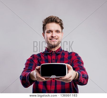 Hipster man in red checked shirt holding virtual reality goggles. Studio shot on gray background
