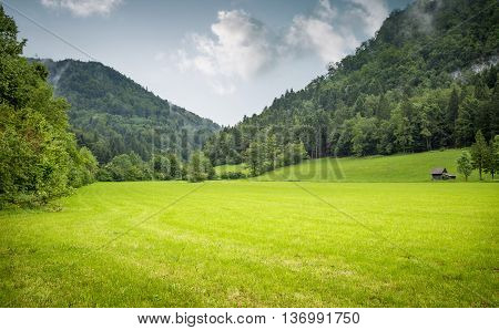 Wooden hut on a beautiful meadow surrounded by mountains