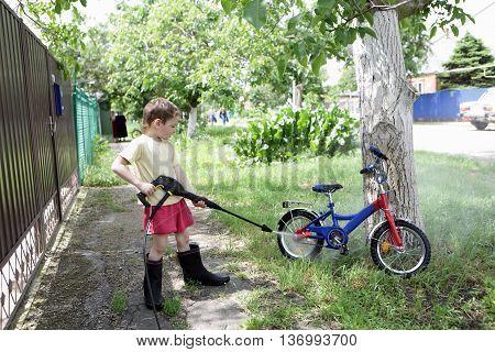 Child washing bike with high pressure washer