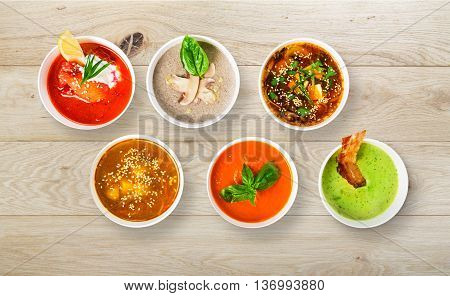 Variety of restaurant hot dishes, healthy food. Japanese miso soup, asian fish soup, russian borscht, english pea soup, mushroom soup, spanish gazpacho on wood. Top view, flat lay.