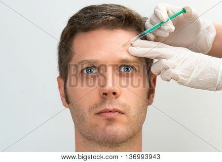 Handsome man is getting injection. Concept of aesthetic beauty. Place for your text.