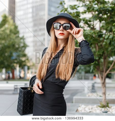 Beautiful Stylish Girl In Black Clothes With Sunglasses And A Hat On The Background Of City. The Con