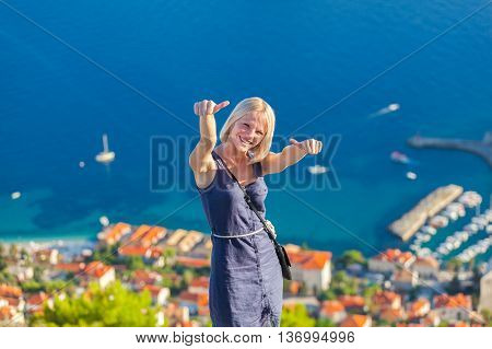 Young female traveler looks to the old city and sea from mountain in Dubrovnik. Summer vacation in Croatia. Euro-trip.