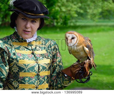 Saffron Walden, Essex, England - June 05, 2016: Woman wearing Elizabethan costume with Barn Owl on Gloved hand.