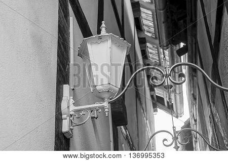 Old vintage iron lantern on the wall made of stone blocks.