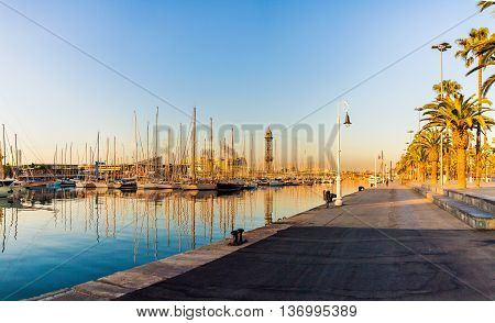 Mooring for yachts and boats in the port of Barcelona at sunrise. The ships moored in the harbor city at sunrise with the reflection of the masts in the water. Spain.