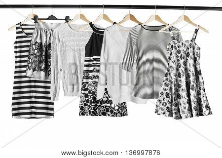 Black and white clothes on clothes racks isolated over white