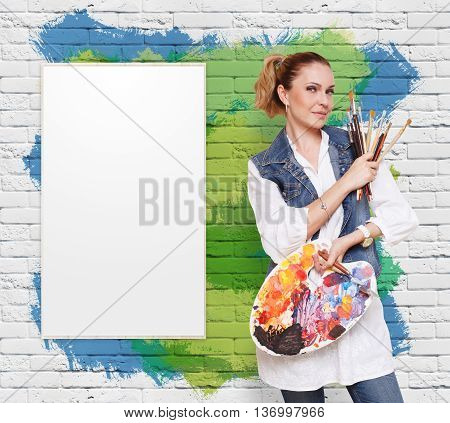 Happy artist. Woman with art tools. Female painter with brushes and palette. Empty easel with canvas at colorful brick wall with copy space. Art classes for adults, education concept.