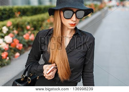 Beautiful Woman In Black Hat And Stylish Clothing Walking On A City