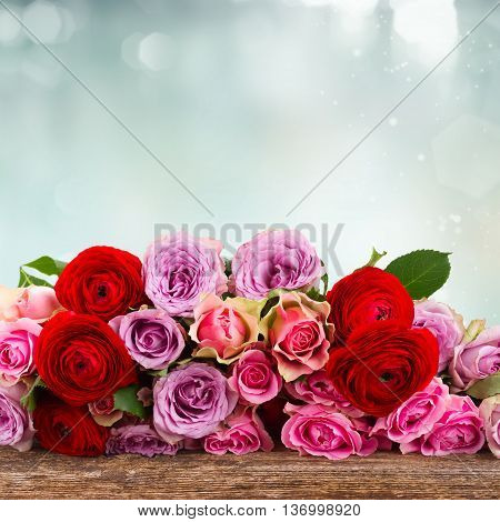 bouquet of fresh roses and ranunculus on wood border with copy space on blue bokeh background