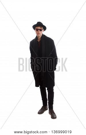 A man in a coat with sunglasses and a fedora