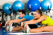 couple in colorful cloths in a gym doing aerobics or warming up with gymnastics and stretching exerc
