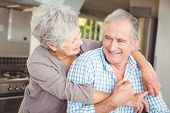 Cheerful senior couple embracing in kitchen at home poster