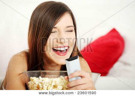 Girl watching TV having fun eating popcorn.