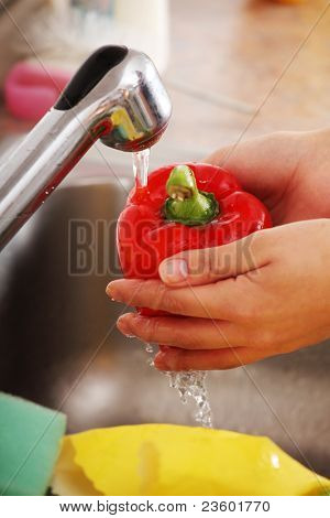 Woman hands washing red paprika