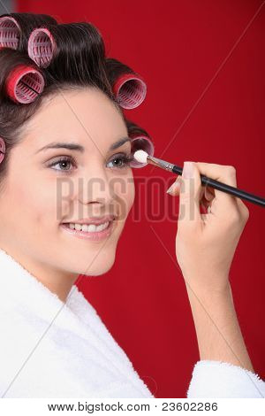 Woman in curlers applying eyeshadow