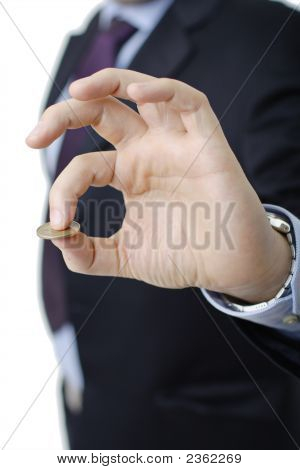 Person In A Suit Holding A Coin In His Hand