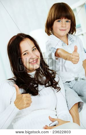 Photo of attractive teenager and her little brother showing thumbs up