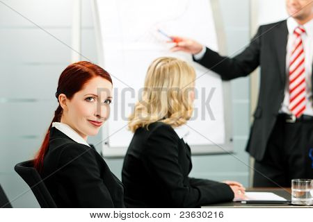 Business - presentation within a team; a colleague is standing on the flipchart