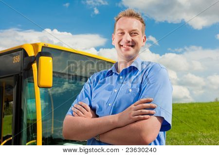 Bus driver is standing in front of his bus under al blue sky