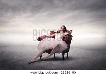 Ballerina relaxing on an armchair