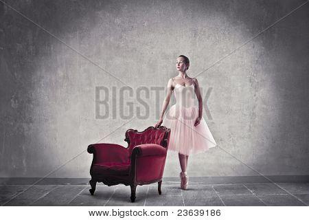 Beautiful ballerina standing beside an armchair
