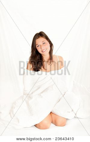Beautiful Young Woman Sitting On White Bed