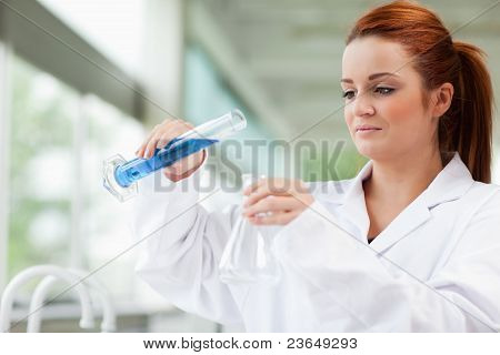 Scientist Pouring Liquid In An Erlenmeyer Flask