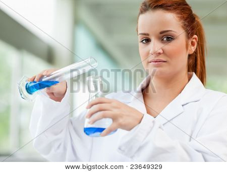 Cute Scientist Pouring Blue Liquid In An Erlenmeyer Flask