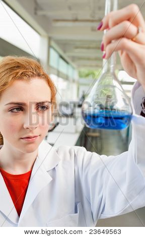 Portrait Of A Cute Science Student Holding A Blue Liquid