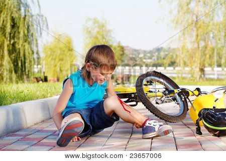 Crying boy with a bleeding injury sitting beside the bike that he has fallen from