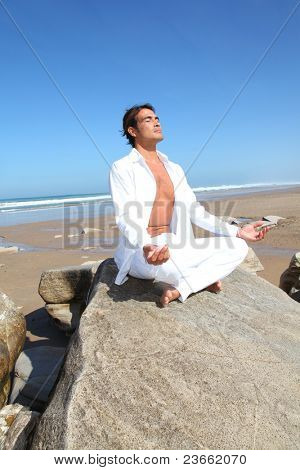 Man doing meditation exercises on the beach