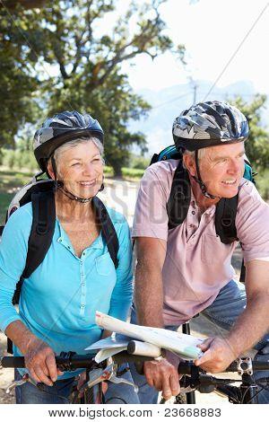 Altes Paar mit Karte auf Land Fahrrad fahren