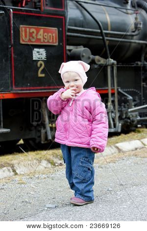 litte girl standing at steam locomotive, Ciernohronska Railway, Slovakia