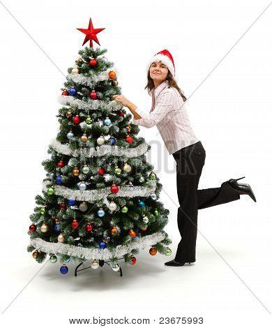 Mujer de pie cerca de árbol de Navidad decorado