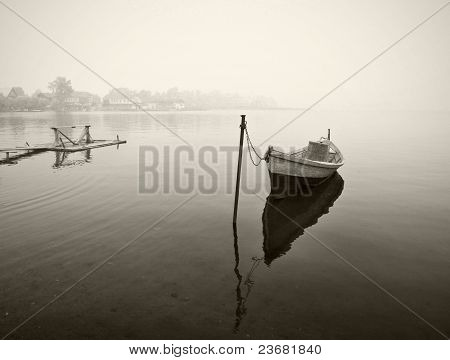 Old wooden boat in fog, black and white