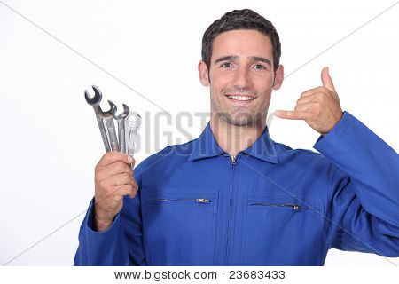 Man with spanners making a call me sign with his hand