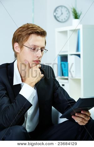 Portrait of a serious accountant looking at calculator tableau
